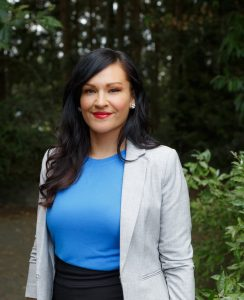 Angela Sterritt pictured from the waist up. Standing outside with trees in the background. She is wearing a grey blazer and a blue shirt. She has dark long hair parted on the side and is smiling.