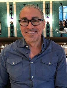 Harlan Pruden facing camera in blue shirt, hair pulled back, black framed glasses, big smile